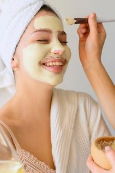 Mulher recebendo uma máscara facial em casa
