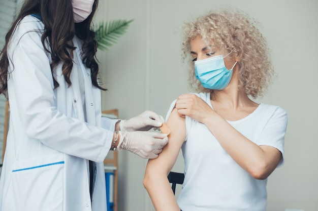 Mulher recebendo vacinação menina feliz protegida por enfermeira equipada com vacina trabalhando