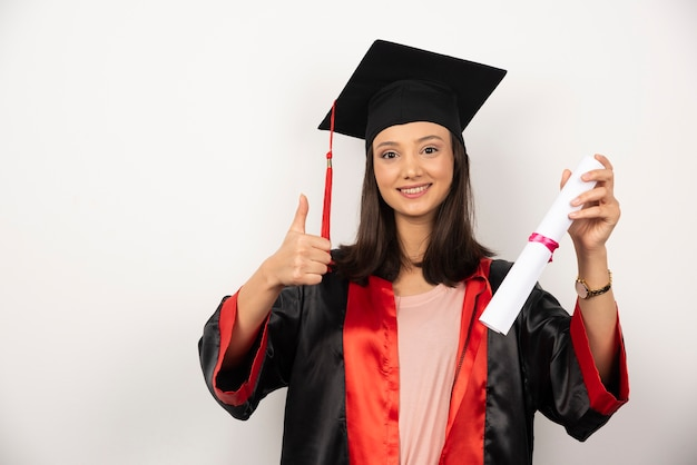 Mulher recém-graduada com diploma fazendo polegares para cima em fundo branco.