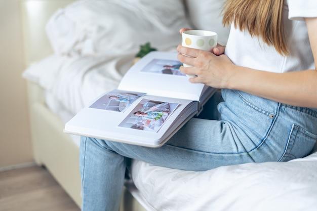 Mulher recortada com as mãos segurando um café e assistindo a um álbum de fotos de família.