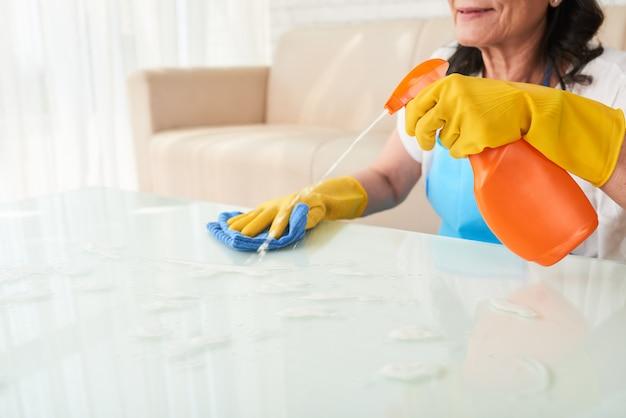 Mulher recortada de pulverização de detergente na mesa de café