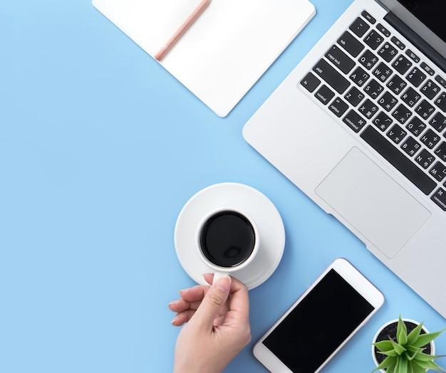 Mulher redatora de blog freelancer bebendo para relaxar em uma mesa limpa e azul clara com café, conceito de trabalho em casa