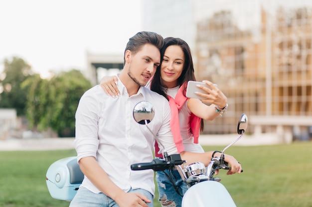 Mulher refinada com cabelo preto e sorriso fofo fazendo selfie com namorado num encontro no fim de semana de verão