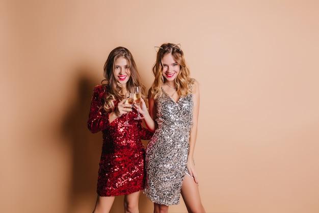 Mulher refinada com sorriso confiante posando na festa de natal com sua adorável irmã