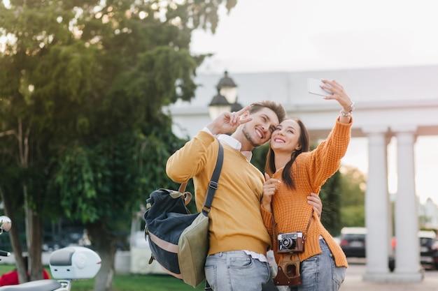 Mulher refinada de cabelos escuros fazendo selfie com um homem bonito em uma camisa laranja com arquitetura branca no fundo