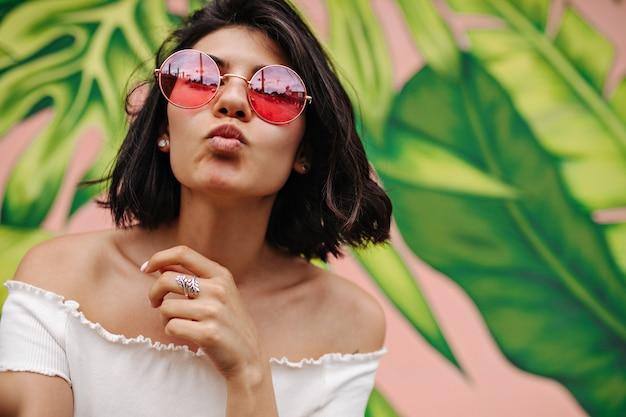 Mulher refinada em óculos de sol rosa posando com expressão facial de beijo