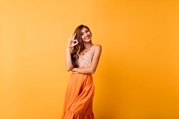 Mulher refinada em saia longa de verão, posando com sinal de tudo bem. foto interna da linda garota caucasiana de pé amarelo.