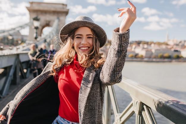 Mulher refinada em um casaco cinza moderno se divertindo durante a sessão de fotos na ponte