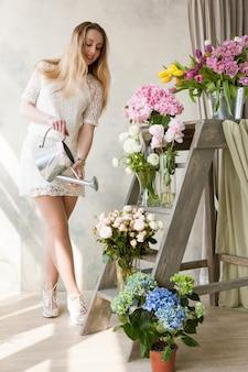 Mulher regando buquês de flores frescas. florista feliz trabalhando em floricultura com buquês frescos