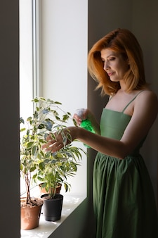 Mulher regando planta tiro médio