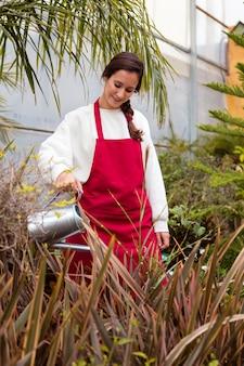 Mulher regando plantas em estufa