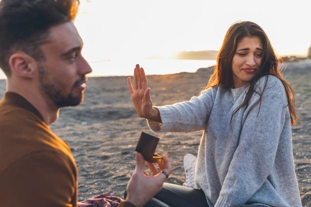 Mulher rejeitando proposta de casamento na costa do mar