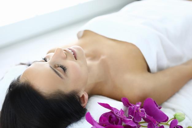Mulher relaxada após massagem com óleo no spa.