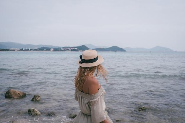 Mulher relaxada, apreciando a baía do oceano, liberdade e vida no litoral da bela praia em tempo nublado ventoso. jovem se sentindo livre, relaxada e feliz. conceito de férias, liberdade, felicidade, gozo