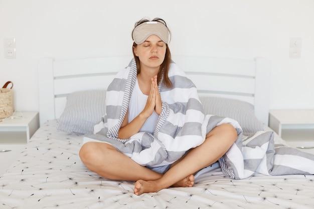 Mulher relaxada calma com máscara de dormir e sendo enrolada em cobertor, sentada na cama com as palmas das mãos unidas, fazendo gesto de oração, mantendo os olhos fechados, posando em sala iluminada interna.
