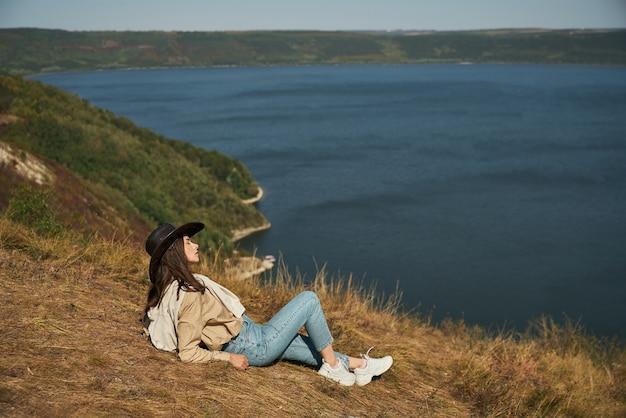 Mulher relaxada com roupa casual e chapéu de cowboy, sentada na colina verde e olhando para a baía de bakota.