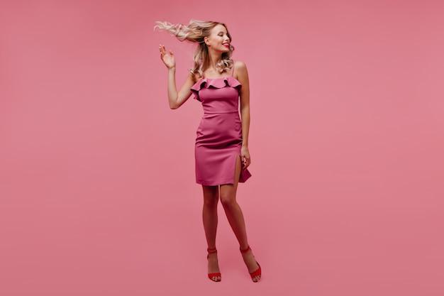 Mulher relaxada com vestido rosa balançando o cabelo