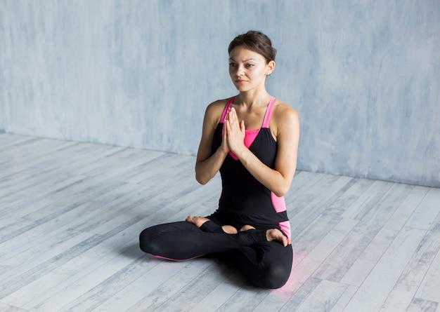 Mulher relaxada, contemplando em uma pose de lótus
