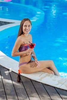 Mulher relaxada de cabelos escuros bebendo um coquetel frio antes de nadar na grande piscina