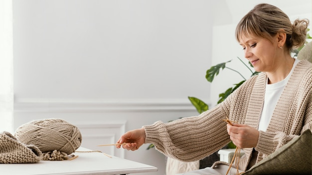 Mulher relaxada de tiro médio tricotando