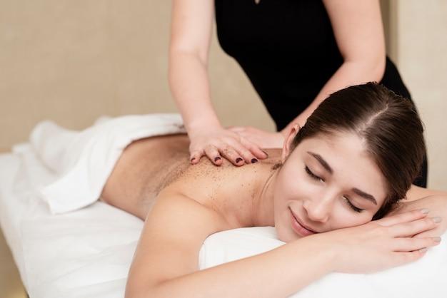Mulher relaxada, desfrutando de terapia de esfoliação