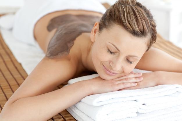 Mulher relaxada, desfrutando de um tratamento de pele de lama
