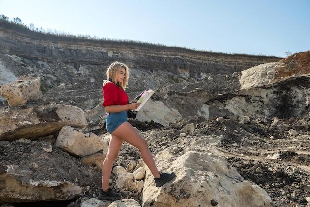 Mulher relaxada e curtindo a natureza, lê o mapa e tira foto nas férias de verão dos sonhos