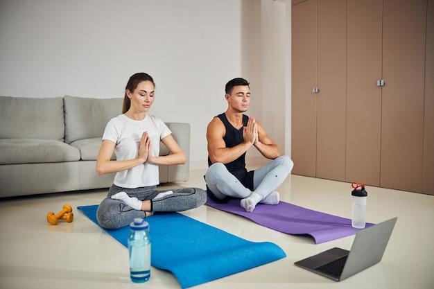 Mulher relaxada e homem concentrado meditando em casa