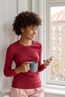 Mulher relaxada e satisfeita posando com o celular em sua casa