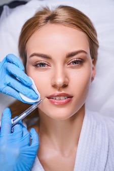 Mulher relaxada está visitando um salão de beleza e tomando botox contra rugas de um cosmetologista com seringa