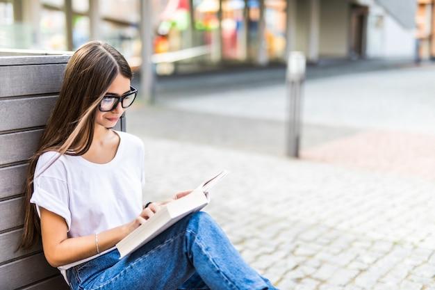 Mulher relaxada, lendo um livro de capa dura ao pôr do sol, sentado num banco