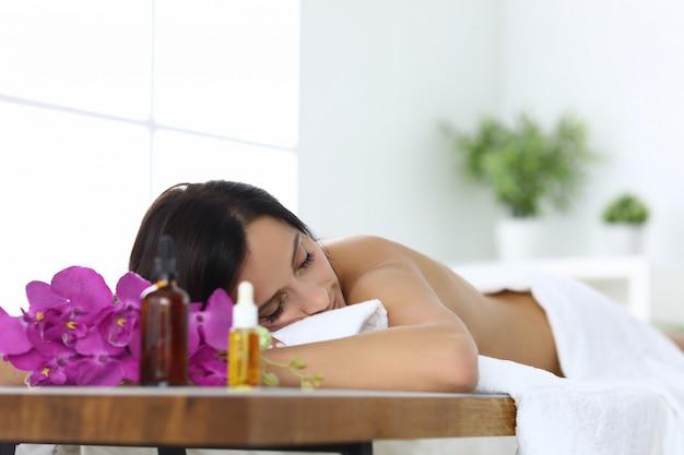 Mulher relaxada no spa encontra-se após massagem closeup