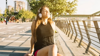Mulher relaxada, ouvindo música no fone de ouvido ao ar livre