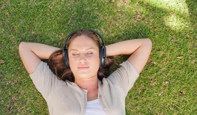Mulher relaxada, ouvir música enquanto estava deitado no gramado