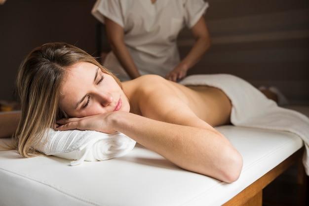 Mulher relaxada recebendo massagem no spa