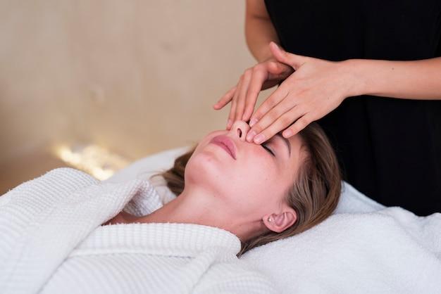 Mulher relaxada, recebendo uma massagem facial