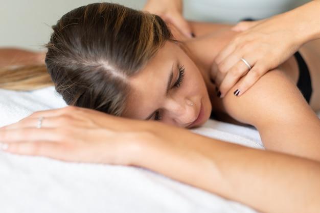 Mulher relaxada, recebendo uma massagem
