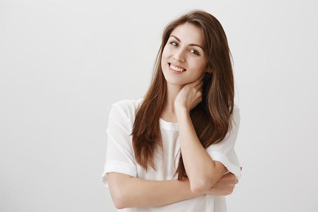 Mulher relaxada satisfeita tocando o pescoço e sorrindo, livrou-se da dor