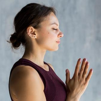 Mulher relaxada, segurando as mãos em uma pose de yoga namastê