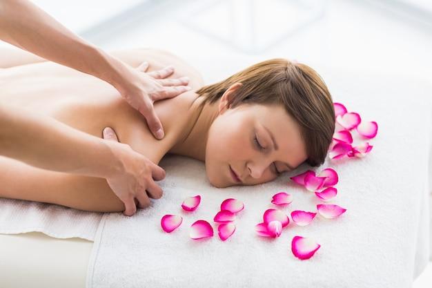 Mulher relaxada sendo massageada por massagista