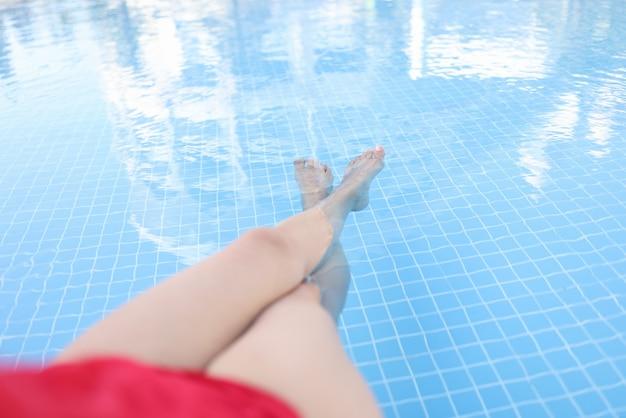 Mulher relaxando as pernas na piscina com água limpa