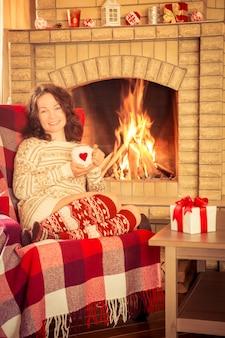 Mulher relaxando em casa perto da lareira. conceito de férias de inverno