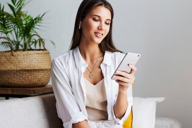 Mulher relaxando em casa, usando smartphone para enviar mensagens de texto, compartilhar fotos, comunicar-se com amigos, verificar e-mail, assistir vídeos, jogar jogos online. oportunidades de entretenimento em dispositivos conectados à web.