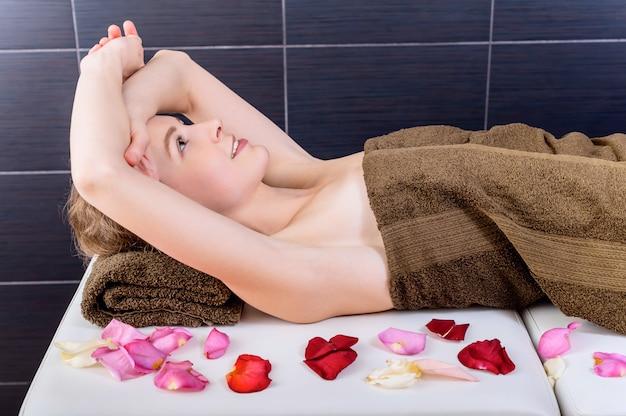 Mulher relaxando em uma mesa de massagem em um salão de spa de quarto escuro