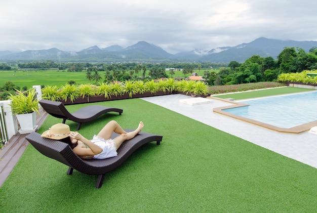 Mulher relaxando em uma piscina infinita olhando para a montanha