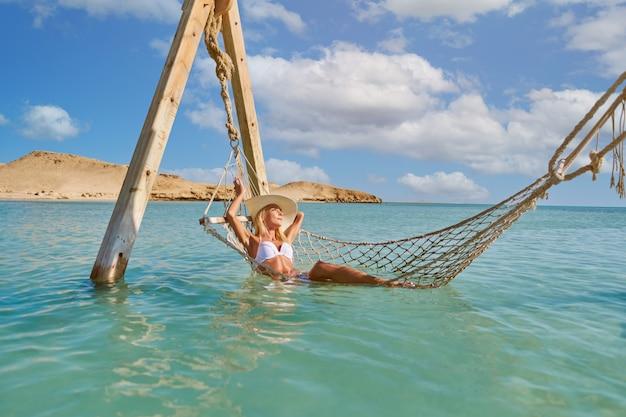 Mulher relaxando em uma rede à beira-mar