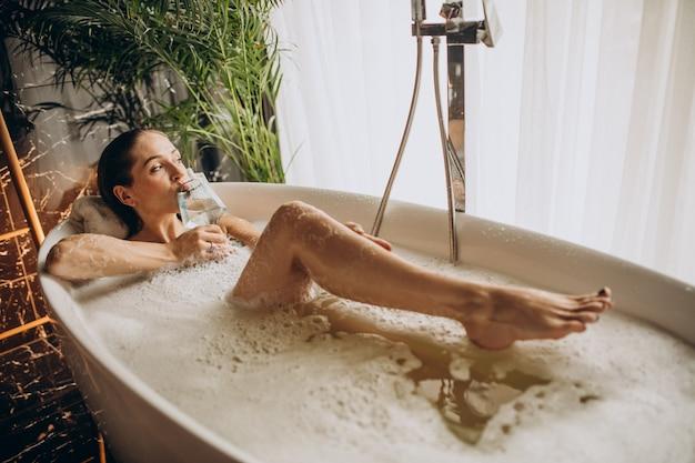 Mulher relaxando na banheira com bolhas e bebendo vinho