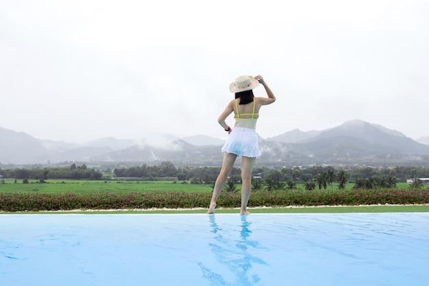 Mulher relaxando na piscina infinita olhando para a vista da montanha