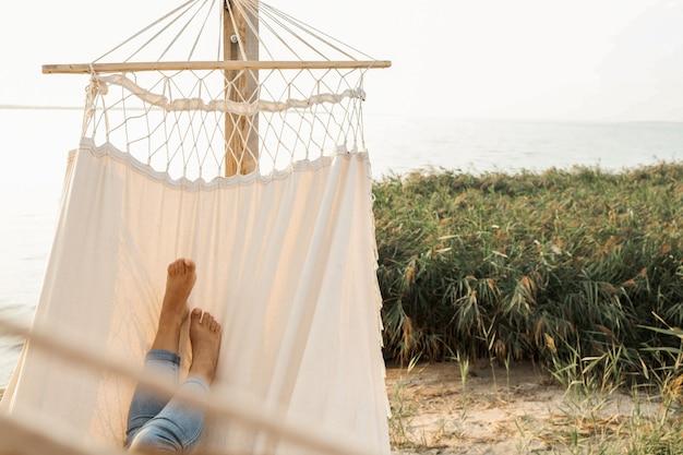 Mulher relaxando na rede na praia