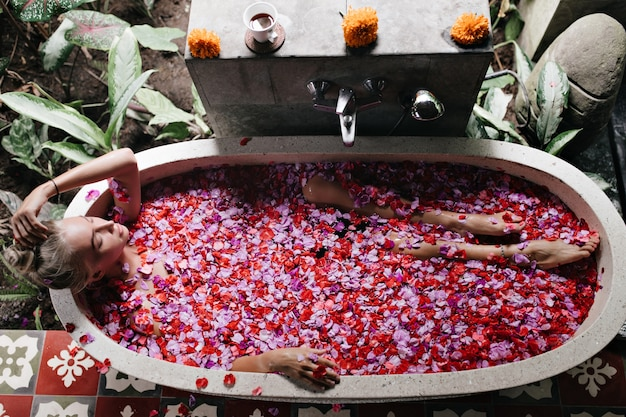 Mulher relaxando no banho. linda loira modelo feminino desfrutando de spa com rosas cor de rosa.